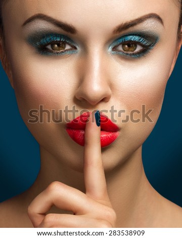 Beautiful Fashion Model With Professional Makeup Making A Hush Gesture On Blue Background - stock photo
