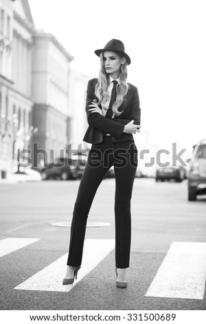 Beautiful fashion model with red lips in a classic man suit walking on the street. Outdoor.