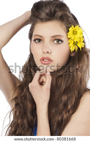 Beautiful fashion portrait of a young and fresh brunette posing with flower in hair