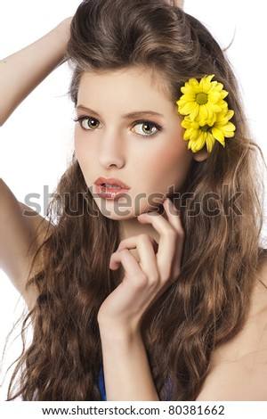 Beautiful fashion portrait of a young and fresh woman with yellow flowers in her hair