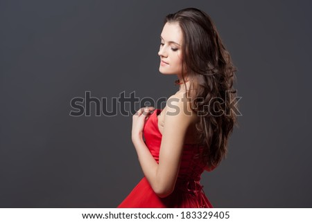 Beautiful fashion portrait of a young woman in a red fluttering dress. Glamour concept. Long hair and perfect body.