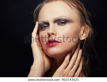 Beautiful fashion portrait of young caucasian woman with grey make-up for party and kissed lips effect. Nails, white eyebrows. Isolated on black background. Studio portrait. Toned
