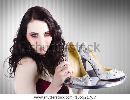 Beautiful fashion sales woman wearing bright make-up holding a silver platter of shoes when selling luxurious evening attire - stock photo