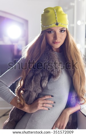 Beautiful fashion sexy elegant girl with long hair, fashionable cap on the head the evening sitting bright makeup and painting near the mirror - stock photo