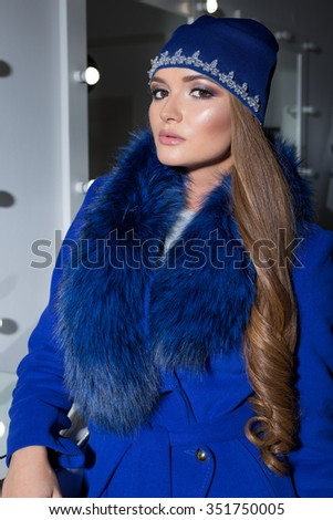 Beautiful fashion sexy elegant girl with long hair trendy blue cap on his head from evening sitting bright makeup and painting near the mirror - stock photo