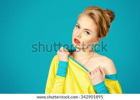 Beautiful fashion woman alluring in vivid colourful clothes over blue background. Bright fashion. Studio shot. - stock photo
