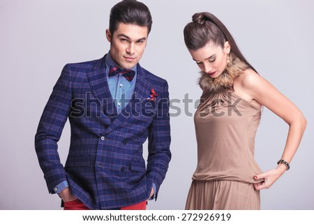 Beautiful fashion woman fixing her dress while her lover is holding his hands in pockets.