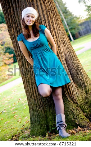 beautiful fashion woman in a park leaning against a tree - stock photo
