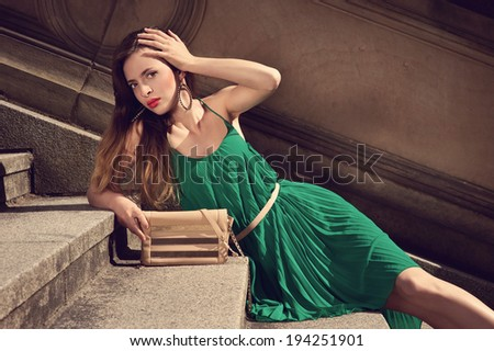 beautiful fashion woman in fashionable green dress and handbag on stairs