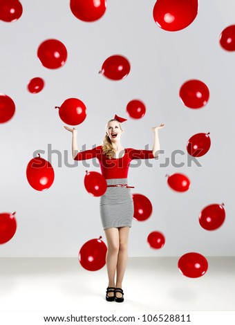 Beautiful fashion woman in red posing with red ballons - stock photo