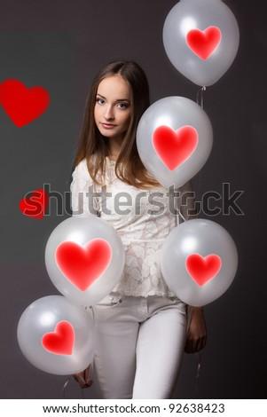 Beautiful fashion woman in studio with white balloons - stock photo