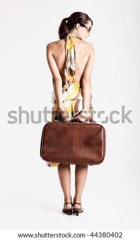 Beautiful fashion woman posing with a vintage suitcase - stock photo