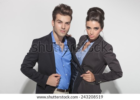 Beautiful fashion woman pulling her boyfriends jacket while both are looking at the camera. - stock photo