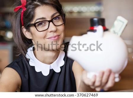 beautiful fashion woman Putting money In Piggy Bank, Indoors - stock photo