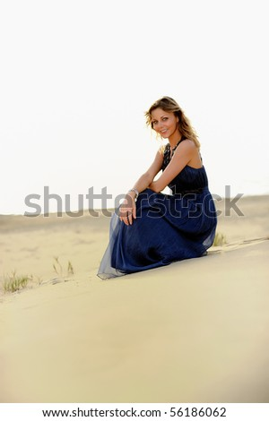 Beautiful fashion woman sitting on the beach in a sand - stock photo