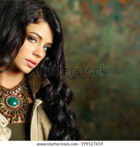 Beautiful fashion woman with curly hair and stage makeup on background - stock photo