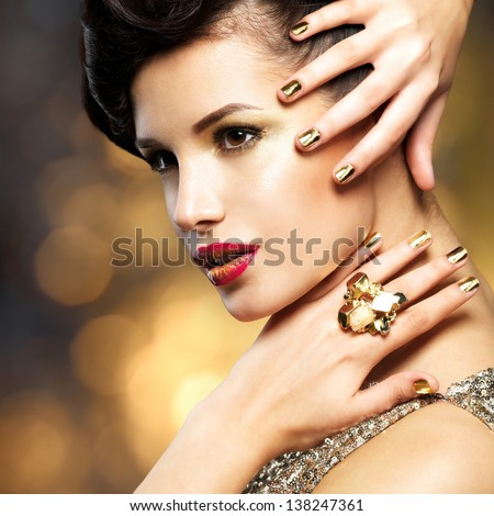Beautiful fashion woman with golden nails and gold ring over style background - stock photo