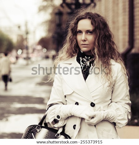 Beautiful fashion woman with long curly hairs in white coat - stock photo