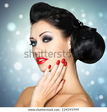 Beautiful fashion woman with red lips, nails and creative hairstyle.  Blinking Background. Bokeh - stock photo