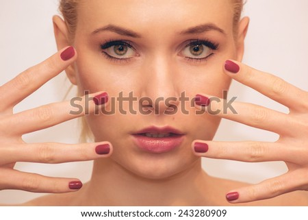 Beautiful fashion woman with red nails posing in studio - stock photo