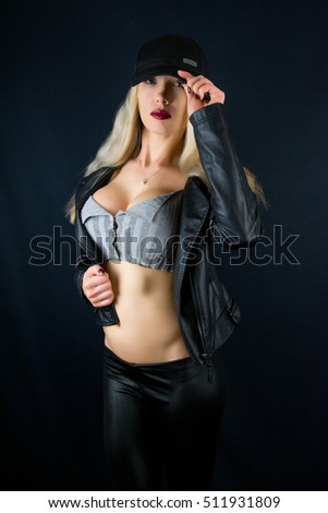 Beautiful fashion woman with slim body on black background in studio / Girl with big breast in new black leather jacket / hot sexy female night style
