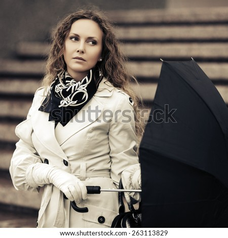Beautiful fashion woman with umbrella on a city street - stock photo