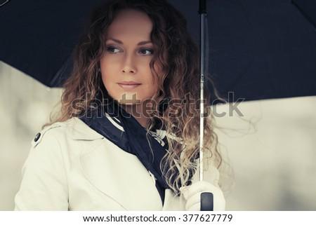 Beautiful fashion woman with umbrella walking on city street - stock photo