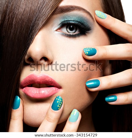 Beautiful fashion young adult girl with turquoise make-up and nails - stock photo