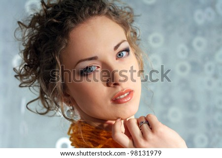 Beautiful Fashion Young Woman in Paper dress.Perfect Makeup. Orange thread lace. Blue background with copy-space