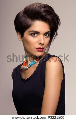 Beautiful fashion young woman looking at camera with trendy hairstyle - stock photo