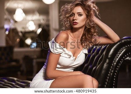 beautiful fashion young woman with curly blond hair on black leather sofa