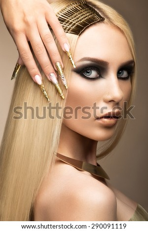 Beautiful fashionable girl in a glamorous image with bright makeup and long gold nails. Art design manicure.  - stock photo