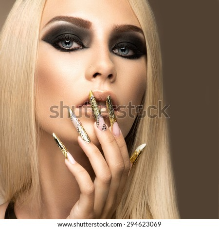 Beautiful fashionable girl in a glamorous image with bright makeup and long gold nails. Art design manicure. Picture taken in the studio.