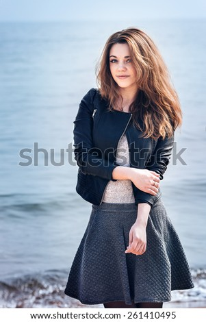 Beautiful fashionable girl in sunglasses and black dress standing on beach - stock photo