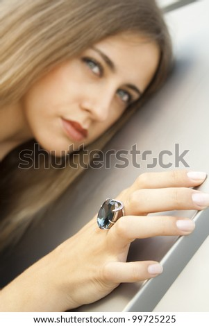 Beautiful fashionable girl on the ring finger is clothed with a large blue gemstone