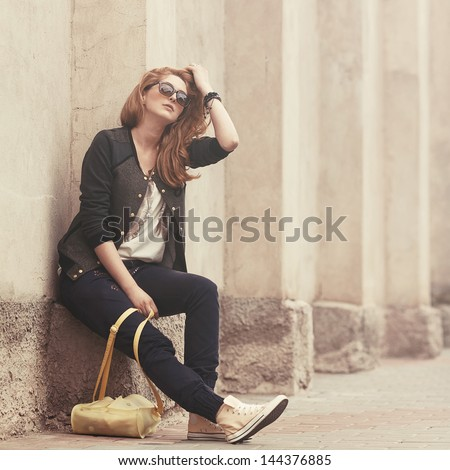 Beautiful fashionable girl sitting in sunglasses with a bag - stock photo