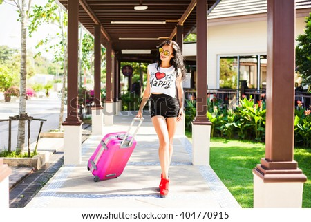 Beautiful fashionable happy girl, hipster, in the terminal at the airport with a pink suitcase. Dressed in a bright cool T-shirt shorts, sunglasses. - stock photo
