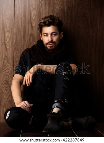 beautiful fashionable man against wooden wall