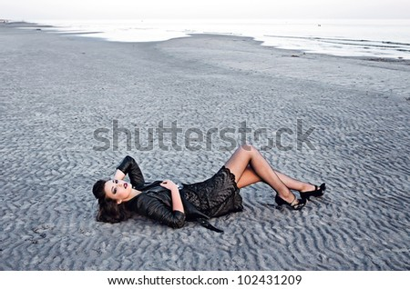 Beautiful fashionable model on the beach in beautiful dress - stock photo