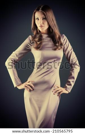 Beautiful fashionable model posing at studio in elegant long dress. - stock photo