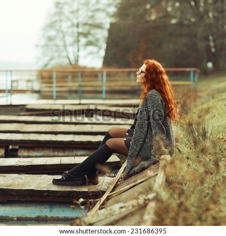 Beautiful fashionable red-haired girl sitting resting near the lake - stock photo