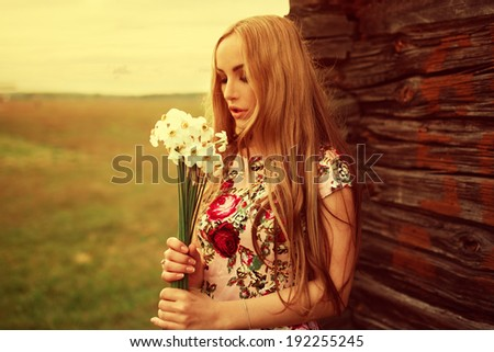 Beautiful fashionable sexy cute girl leaning against the house stands with flowers - stock photo
