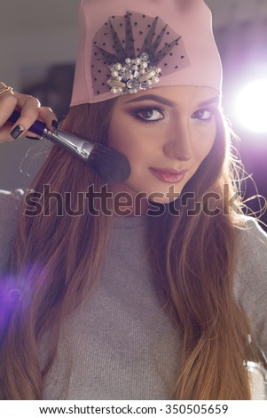 Beautiful fashionable sexy elegant devkshka with long hair fashionable cap on his head with an evening sitting bright makeup and painted near the mirror - stock photo