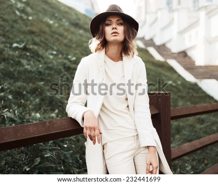 Beautiful fashionable woman in a hat and coat posing - stock photo