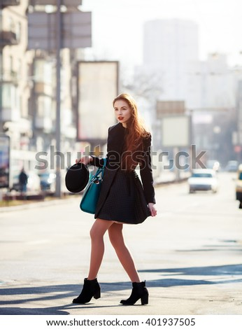 Beautiful fashionable woman in a hat and coat posing outside in a city street