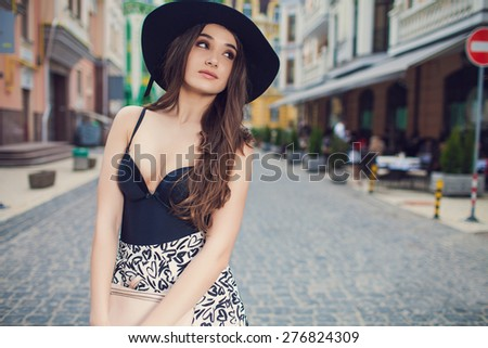 Beautiful fashionable woman in a hat walking on the street