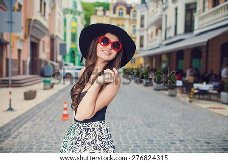 Beautiful fashionable woman in a hat walking on the street - stock photo