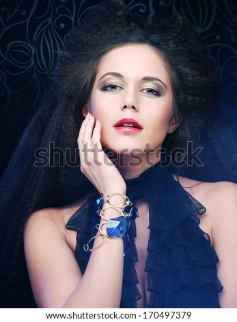 Beautiful fashionable woman in black dress. Studio shot.