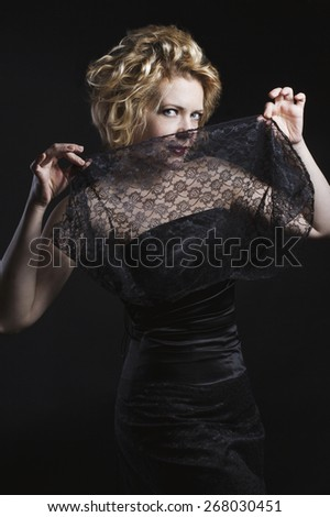 Beautiful fashionable woman in black dress with a veil