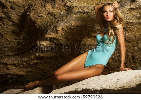 Beautiful fashionable woman in blue bikini in the rock - stock photo
